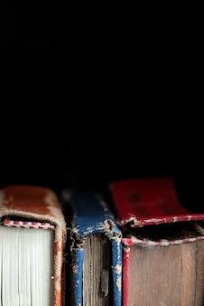Close-up van oude boeken op zwarte achtergrond met exemplaarruimte wordt geschoten voor tekst die.
