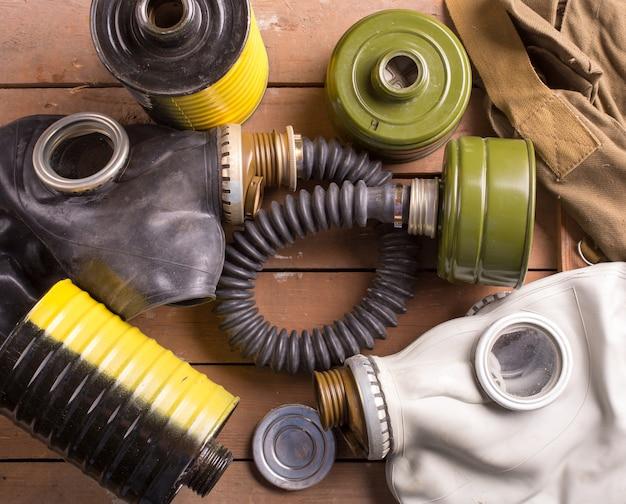 Close-up van oude gasmaskers en filters op houten kist