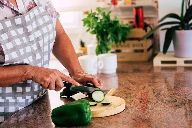 Close-up van oude volwassen vrouwenhanden die groenten snijden en koken voor een gezonde lunch of diner thuis, dagelijkse keukenscène met grootmoeder aan het werk