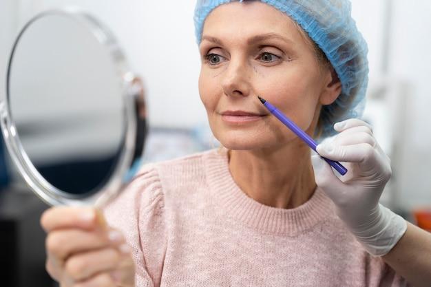 Close-up van oude vrouw die in de spiegel kijkt