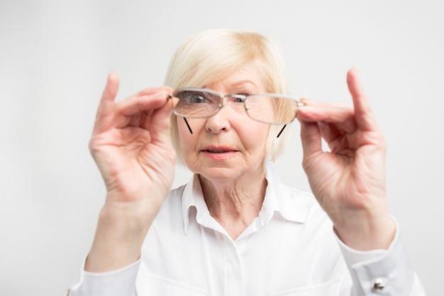 Close up van oude vrouw is zeer attent op details. ze kijkt naar haar bril en probeert daar vuile plekken te vinden. ze houdt ervan dat alles schoon blijft.