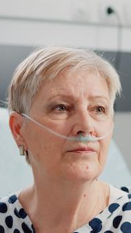 Close up van oude vrouw zittend in bed met hartslagmeter