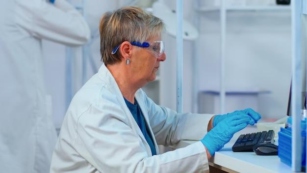 Close up van oudere chemicus vrouw typen op computer in modern uitgerust laboratorium. multi-etnische dingen die vaccinevolutie analyseren met behulp van hightech voor onderzoek naar behandeling tegen covid19-virus