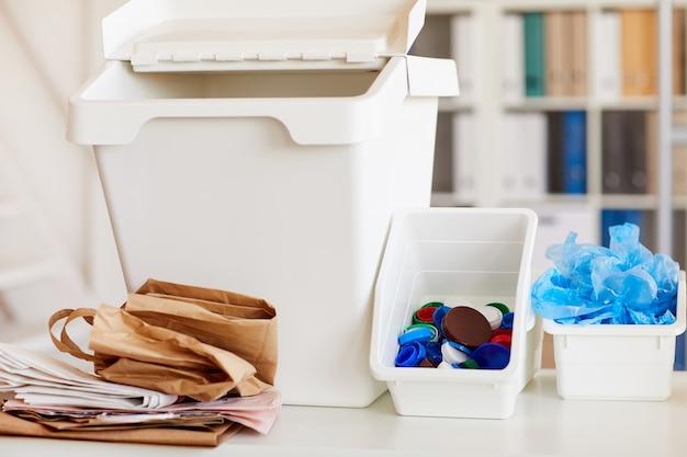 Close-up van ovarious afvalitems gesorteerd op materiaalsoort en klaar voor recycling in kantoorinterieur