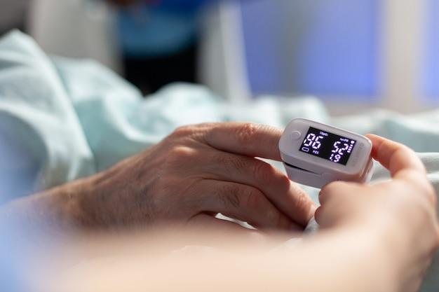 Close up van oxymeter bevestigd op zieke senior patiënt