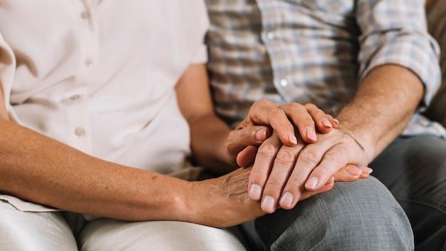 Close-up van paar dat elkaars hand houdt