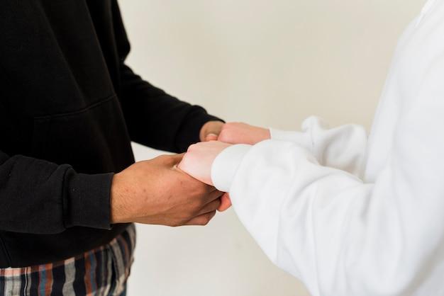 Close-up van paar dat elkaars handen houdt tegen witte achtergrond