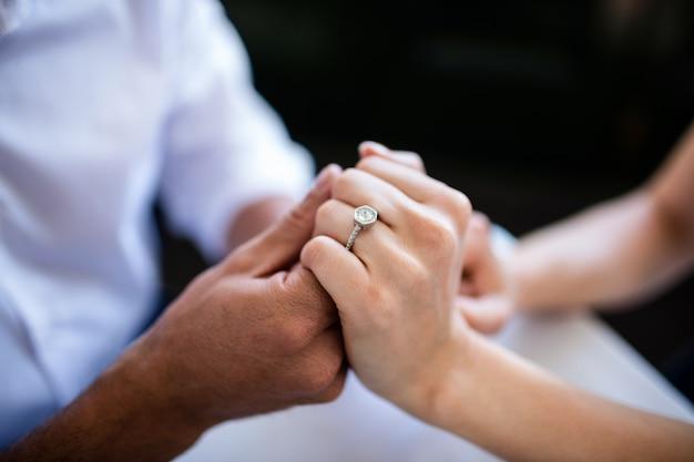 Close-up van paar hand in hand met verlovingsring