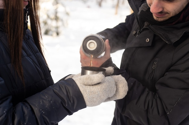 Close up van paar handen met kopje thee en thermos in winter park
