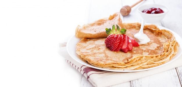 Close-up van pannenkoeken met slagroom en aardbeien