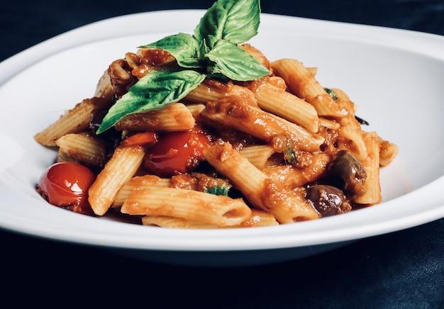 Close-up van pasta met sauzen en vlees in een kom op tafel onder de lichten