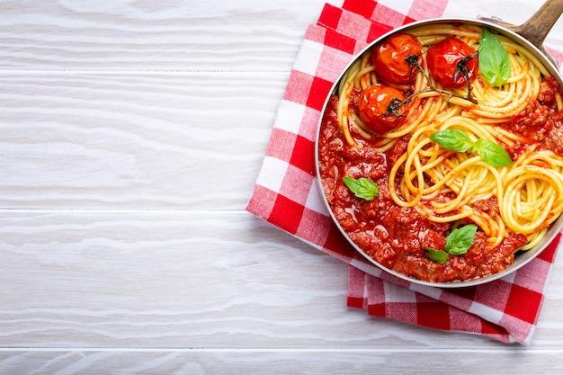 Close-up van pasta spaghetti met vlees en tomaat bolognese saus in een pan geserveerd met basilicum en kerstomaatjes op witte houten rustieke achtergrond, bovenaanzicht. traditioneel italiaans diner, ruimte voor tekst
