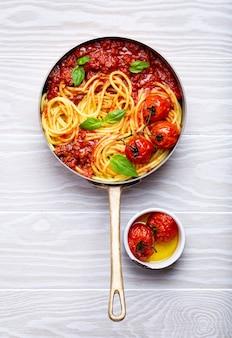 Close-up van pasta spaghetti met vlees en tomaat bolognese saus in een pan geserveerd met basilicum en kerstomaatjes op witte houten rustieke achtergrond, bovenaanzicht. traditioneel italiaans diner