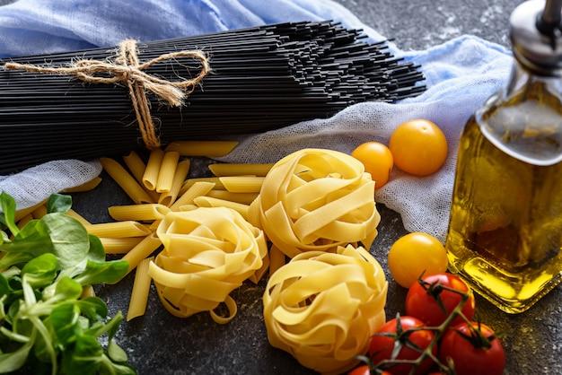 Close-up van pastavariëteiten - zwarte spaghetti met inktvisinkt, fettuccine, rode en gele tomaten, fles olijfolie op grijze achtergrond, italiaanse keukenconcept