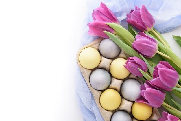 Close-up van pastel blauwe en gele paaseieren met violette tulpen met blauw doek servet op witte achtergrond met kopie ruimte