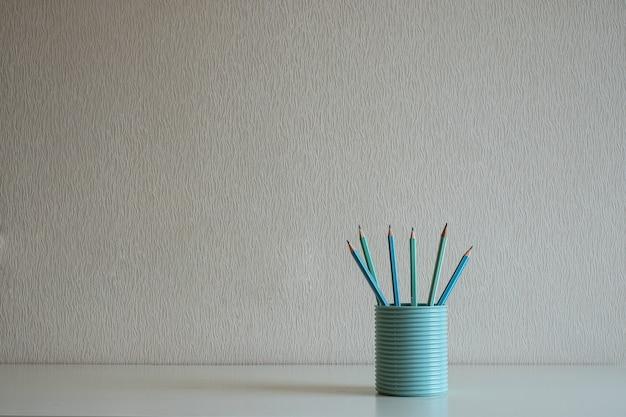 Close-up van pastelpotloden in het blauwe glas op het bureau bij grijze muurachtergrond