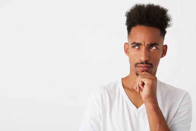 Close-up van peinzende aantrekkelijke jonge man met krullend haar draagt t-shirt ziet er attent uit en denkt geïsoleerd over witte muur kijkt naar de zijkant