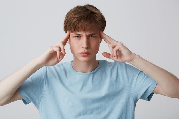 Close-up van peinzende gespannen jonge man draagt blauwe t-shirt wat betreft zijn slapen, denkend en met hoofdpijn geïsoleerd over witte muur
