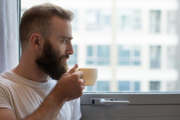 Close-up van peinzende hipster man koffie drinken uit de beker