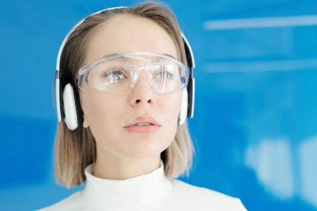 Close-up van peinzende jonge vrouw in innovatieve bril en draadloze koptelefoon rondkijken