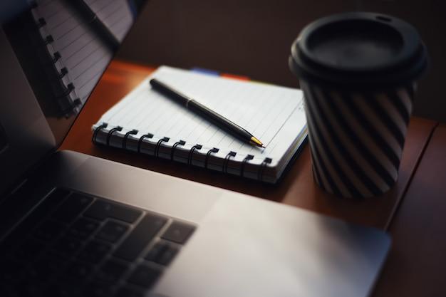 Close-up van pen en notitieboekje op bureau dichtbij laptop en koffiekop.