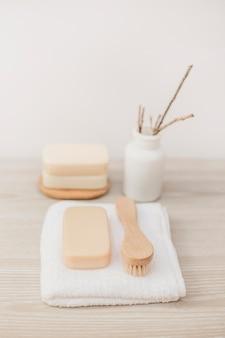 Close-up van penseel; zeep en handdoek op houten oppervlak