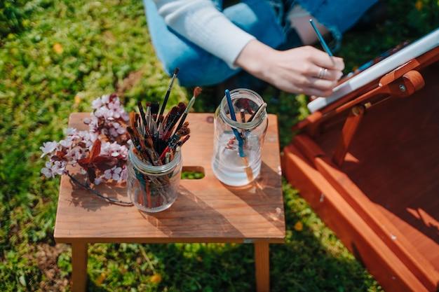 Close-up van penselen in vele maten van een jonge kunstenaar terwijl ze een foto in een park schildert