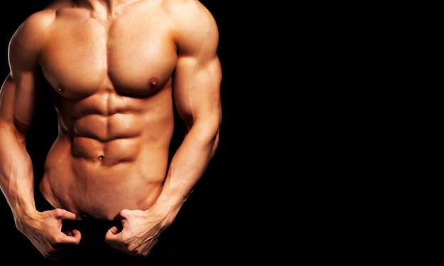 Close up van perfect mannelijk lichaam geïsoleerd op zwarte achtergrond met kopie ruimte