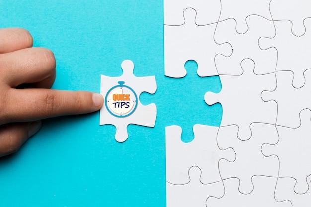 Close-up van persoon aanraken witte puzzel met snelle tips tekst op stopwatch klok
