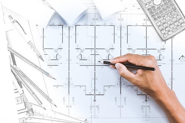 Close-up van persoon de tekeningsplan van de ingenieurshand op blauwdruk met architecteninstrument bij bureau.