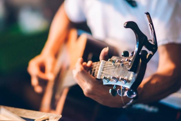 Close-up van persoon die gitaar speelt met onscherpe achtergrond