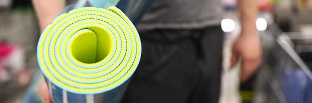 Close-up van persoon die groene zachte matten voor yoga of stretching.