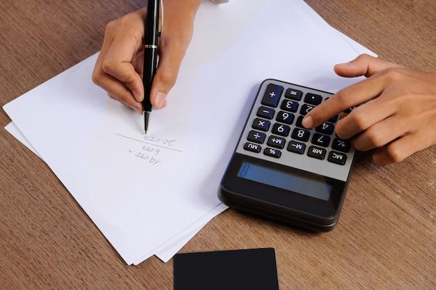 Close-up van persoon die op calculator en het schrijven berekent