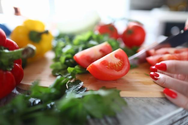 Close-up van persoon die rijpe tomaat op plakjes snijdt. rode en gele paprika's met groen op tafel. verse zomergroenten. gezond eten en smakelijk lunchconcept