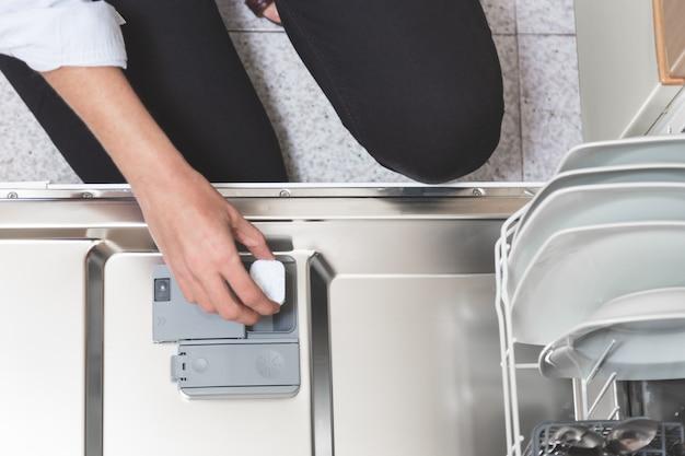 Close-up van persoon hand zetten vaatwasser zeep tablet in wasmiddel vaatwasser doos