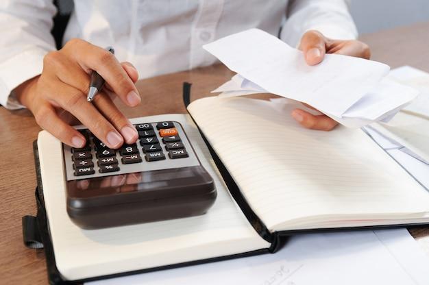 Close-up van persoon het berekenen rekeningen op calculator