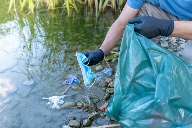 Close-up van persoon masker en handschoenen verzamelen uit de rivier. man schoonmaken rivier van kunststoffen. milieu concept.