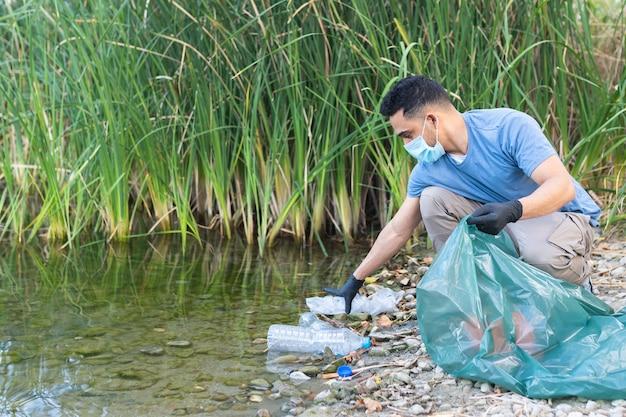 Close-up van persoon plastic verzamelen uit de rivier. man schoonmaken rivier van kunststoffen. milieu concept.