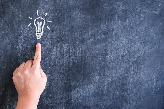 Close-up van persoon wijzende vinger op getekende gloeilamp met krijt over blackboard