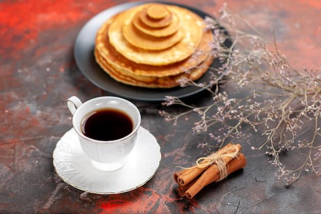 Close-up van pluizige pannenkoeken en een kopje thee naast kaneelkalk