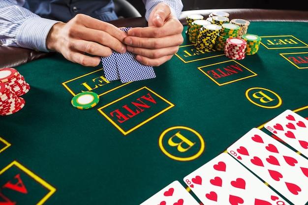 Close up van pokerspeler met speelkaarten en chips aan groene casino tafel.
