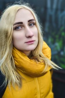 Close-up van portret van blonde hipster tiener meisje selfie maken, ze draagt gele jas en rugzak, wandelen buiten door ondergrondse passage en selfie maken