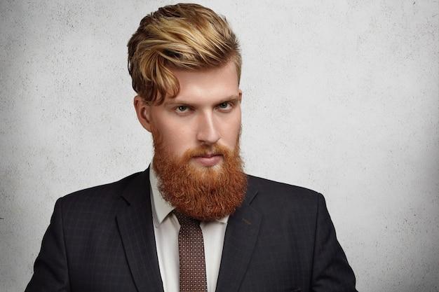 Close-up van portret van knappe jonge corporate werknemer met stijlvol kapsel en dikke baard elegante pak dragen kijken met ernstige en gerichte gezichtsuitdrukking voor zakelijke bijeenkomst