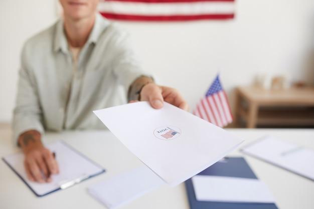 Close-up van portret van lachende jongeman papieren overhandigen aan mensen tijdens het registreren van kiezers bij het stembureau op verkiezingsdag, kopieer ruimte