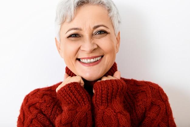 Close-up van portret van modieuze zestig-jarige europese vrouwelijke gepensioneerde m / v in gezellige gebreide trui poseren isoolated met blij dolgelaatsuitdrukking, gebalde vuisten, groot nieuws vieren