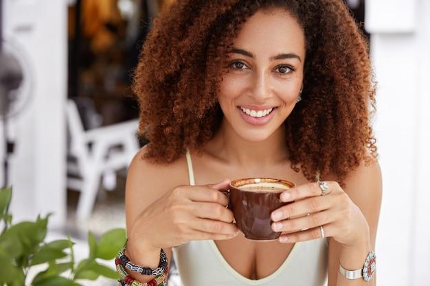 Close up van positieve afro-amerikaanse vrouwelijke model houdt kopje koffie en kijkt gelukkig naar camera, recreëert in gezellig restaurant na een zware werkdag