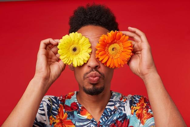 Close-up van positieve jonge afro-amerikaanse jongen, draagt in hawaiiaans shirt, kijkt naar de camera via bloemen met vrolijke uitdrukking, kus naar de camera sturen, staat op rode achtergrond.