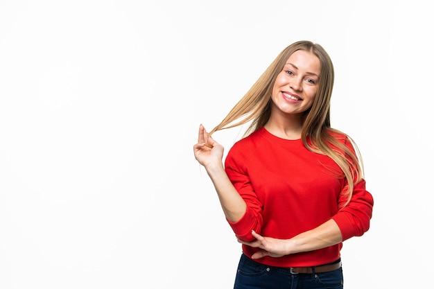Close-up van positieve jonge vrouw die haar haar aanraakt dat op wit wordt geïsoleerd