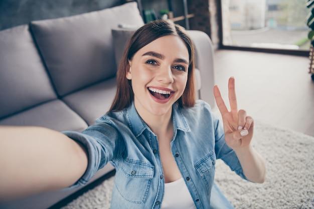 Close up van positieve vrolijke studente maken selfie show vsign