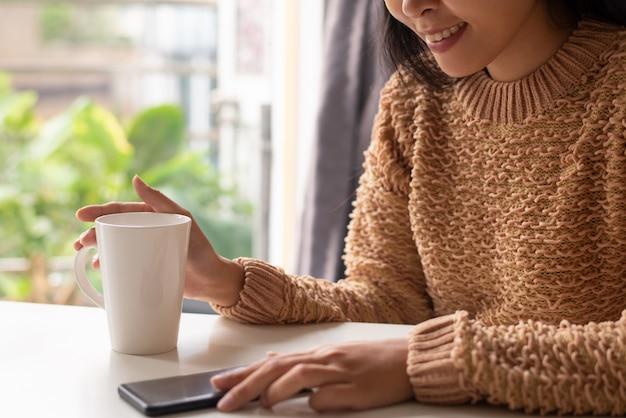 Close-up van positieve vrouw die online nieuws op smartphone bekijkt